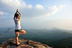 妇女实践瑜伽在日出海边 库存图片