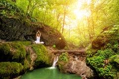 妇女实践瑜伽在瀑布 sukhasana姿势 免版税库存照片