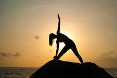 妇女实践瑜伽在黎明,有在石头、黎明和女孩的图象的一asana,享受黎明,满意对lif 免版税库存照片