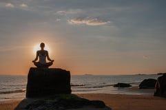 妇女实践瑜伽坐在莲花姿势的石头在日落 思考在海滩的妇女剪影 库存图片