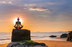妇女实践瑜伽坐在莲花姿势的石头在日落 思考在海滩的妇女剪影 库存照片
