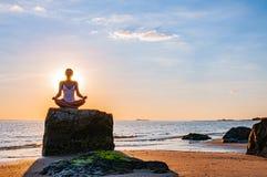 妇女实践瑜伽坐在莲花姿势的石头在日落 思考在海滩的妇女剪影 免版税库存照片