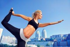 妇女实践的国王舞蹈家瑜伽姿势 免版税库存照片