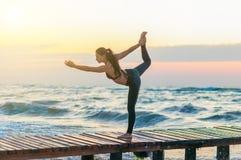 妇女实践的战士瑜伽姿势户外在日落天空背景 免版税库存图片