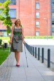 妇女实践的走在拐杖 免版税库存图片