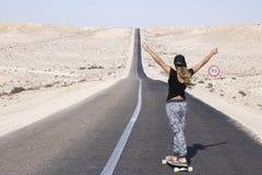 妇女实践的longboard用长的路 免版税库存照片