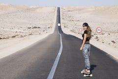 妇女实践的longboard用长的路 免版税图库摄影