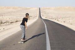 妇女实践的longboard用长的路 图库摄影