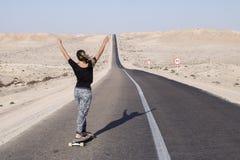 妇女实践的longboard用长的路 库存照片