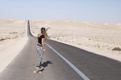 妇女实践的longboard用长的路 免版税库存图片