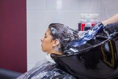 妇女客户的美发师洗涤的头发 免版税库存照片