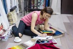 妇女室内设计师、与织品一起使用样品帷幕的和窗帘 事务-纺织工业 免版税库存照片