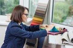 妇女室内设计师、与织品一起使用样品帷幕的和窗帘 免版税库存照片
