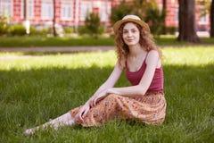 妇女室外画象 愉快的年轻女人坐绿草在公园在夏天,迷人的女性佩带的地板裙子,偶然 免版税库存照片