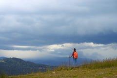 妇女宽射击有远足的杆在山山顶 免版税库存图片
