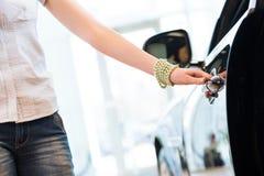 妇女对一辆新的汽车打开门 免版税库存照片