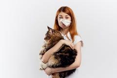 妇女对在灰色背景的一只猫是过敏的 库存照片