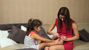 妇女对女孩孩子的切制钉 当母亲切开她的钉子时,女孩坐沙发 股票视频