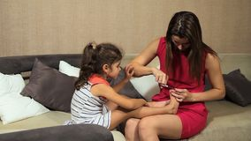 妇女对女孩孩子的切制钉 当母亲切开她的钉子时,女孩坐沙发 影视素材