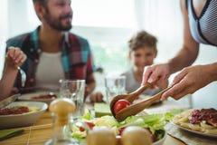 妇女对她的家庭的服务膳食 库存图片