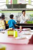 妇女对学童的服务食物 图库摄影