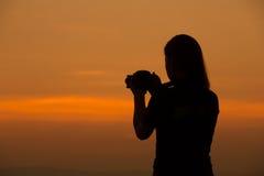 妇女射击剪影与照相机的在日落 库存照片
