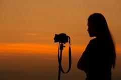 妇女射击剪影与照相机的在日落 免版税库存照片