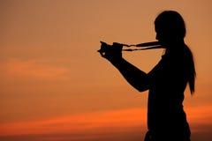 妇女射击剪影与照相机的在日落 免版税库存图片