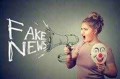 妇女尖叫在传播假新闻的扩音机 库存图片