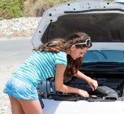 妇女尝试对repear她残破的汽车 图库摄影