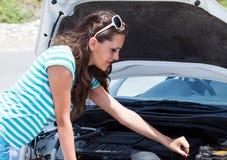 妇女尝试对repear她残破的汽车 库存图片