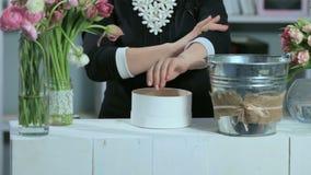 妇女展示在圆的形式白色箱子的花的布置 股票录像