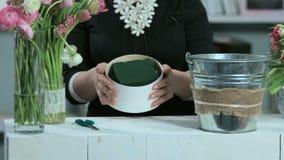 妇女展示在圆的形式白色箱子的花的布置 影视素材