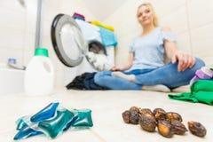 妇女展示肥皂坚果和胶凝体荚洗涤剂 图库摄影