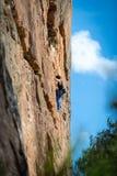 妇女岩石攀登垂直的峭壁面孔在墙壁搬运工通过百年幽谷电路的壁架 免版税库存照片