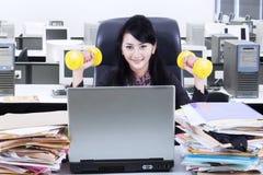 妇女工作和锻炼在办公室 库存图片
