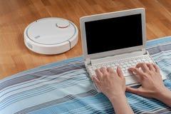 妇女工作在计算机在客厅,当机器人吸尘层压制品的地板时的吸尘器 自动化家庭作业,帮助溃败 库存照片