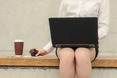 妇女工作在计算机并且吃巧克力蛋糕 库存图片