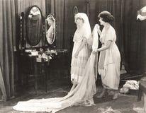 妇女帮助的新娘换衣服 免版税库存照片