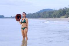 妇女帽子和样式比基尼泳装在海滩 库存照片