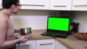 妇女干净的盘和观看的膝上型计算机有绿色屏幕的在厨房里 影视素材