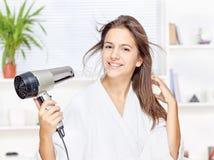 妇女干毛发在家 免版税库存照片