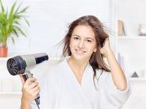 妇女干毛发在家 库存照片