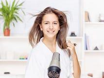妇女干毛发在家 库存图片