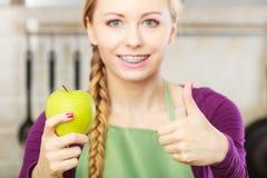 妇女年轻主妇在厨房里用苹果果子 免版税库存图片