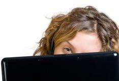 妇女年轻人的接近的耳机膝上型计算&# 库存图片