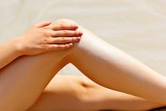 妇女应用太阳在她光滑的被晒黑的腿的保护奶油 图库摄影