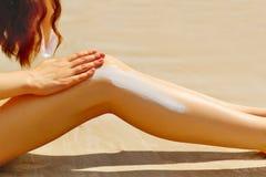 妇女应用太阳在她光滑的被晒黑的腿的保护奶油 库存照片