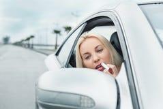 妇女应用看在汽车镜子的玫瑰色唇膏 免版税库存照片