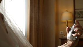 妇女应用香水于她的脖子在她的婚礼那天在酒店房间 匿名在慢动作的妇女喷洒的芬芳 股票视频